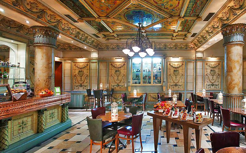 The grand hotel restaurant at the Imperial Hotel, Cork, with tables set up for dinner and marble columns, walls and ceiling