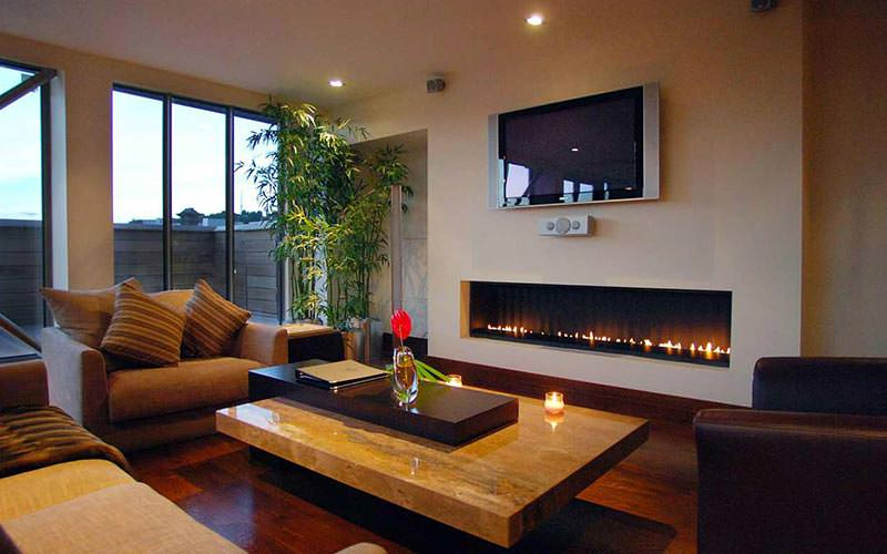 Two chairs and a sofa set around a coffee table, in front of a lit fire and a TV on the wall