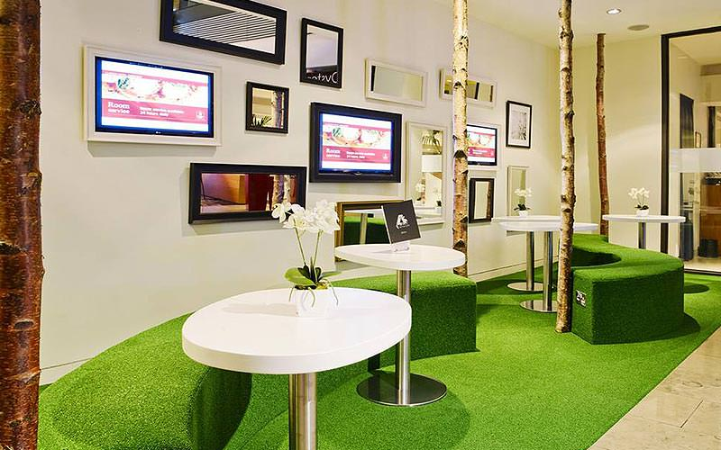 Tables and green stool seats, set on a green carpet in front of a white wall of pictures