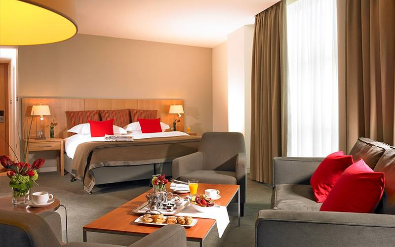A double bed in a hotel room, topped with red cushions, with grey seats and a sofa around a coffee table in the foreground