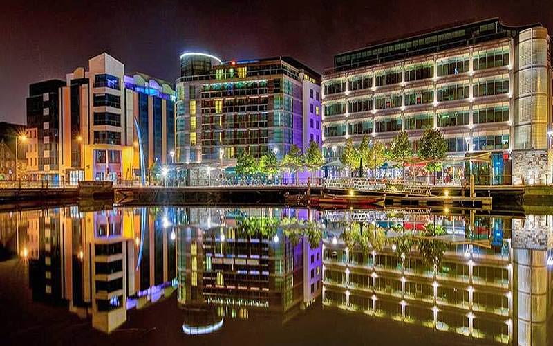 The exterior of Clarion Hotel Cork lit-up, and other adjacent buildings, on the banks of the river at night