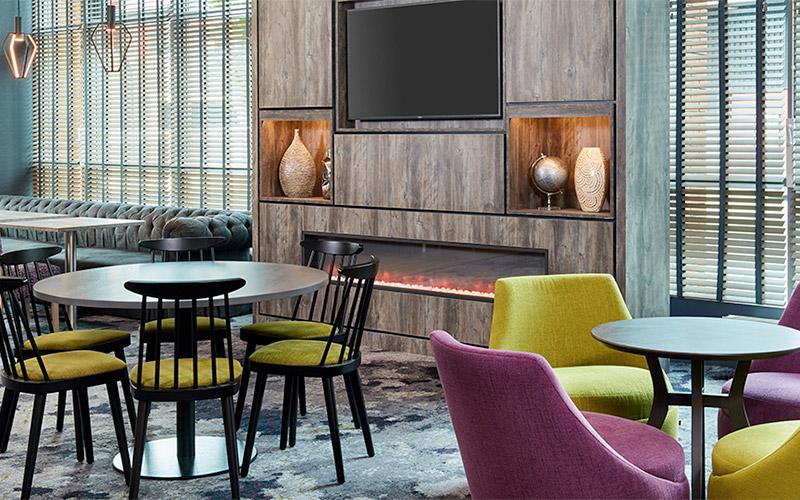 Six bar stools in a room facing a TV
