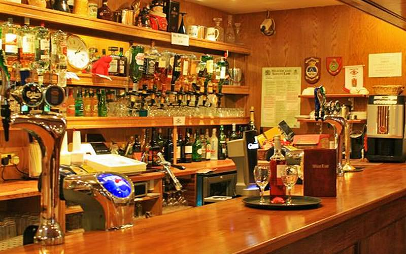 A small, traditional wooden bar with lots of spirits lined up behind the bar
