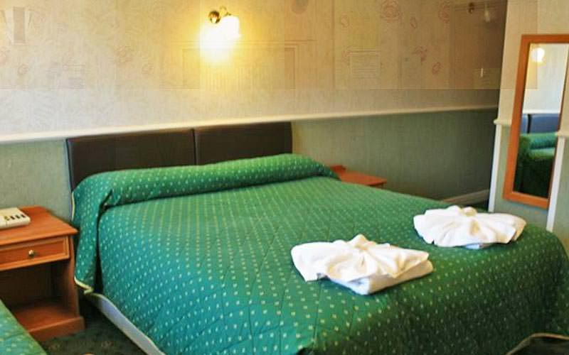 A double bedroom with green bedding and two towels folded into flower shapes on the bottom
