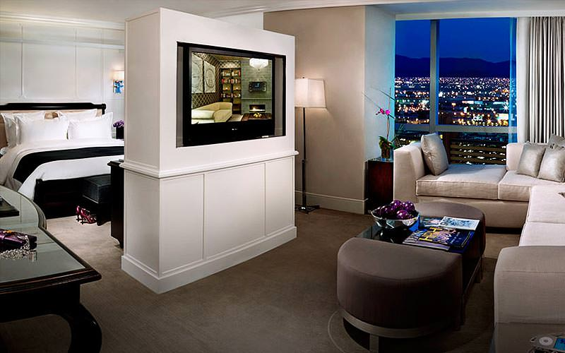 A corner sofa, spinning TV and double bed in a Hard Rock Hotel guest room