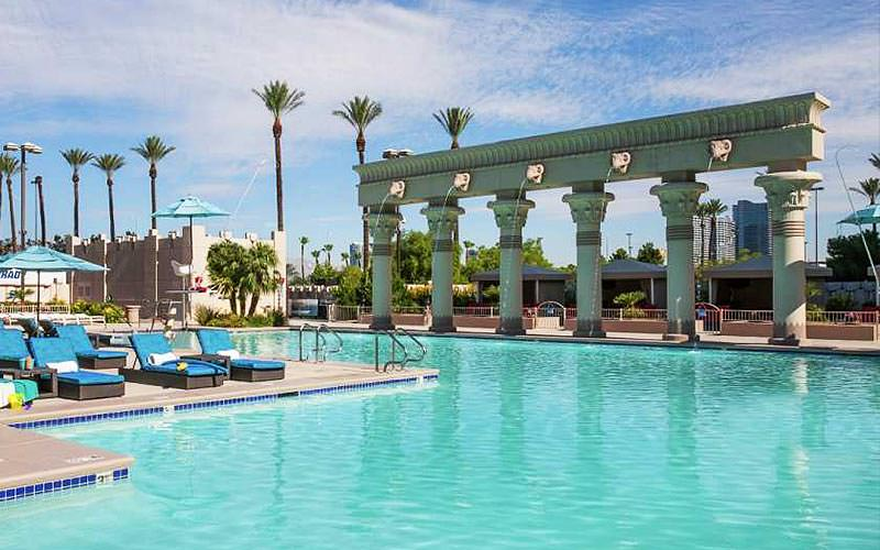 An Egyptian themed outdoor pool with decorative columns and fountains