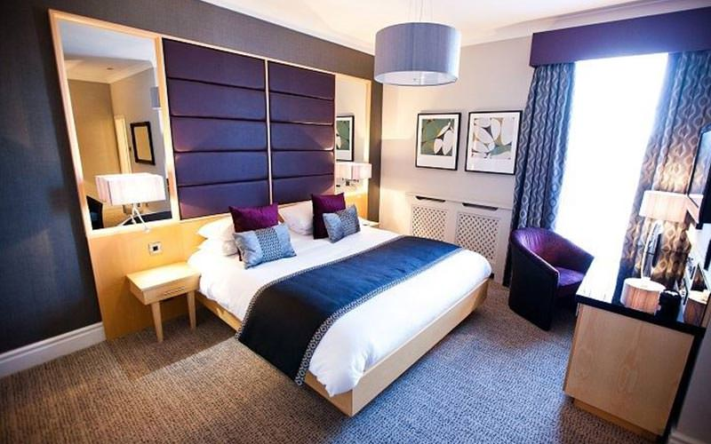 A double bed topped with a throw and cushions, facing a desk and chair, in a purple hotel room