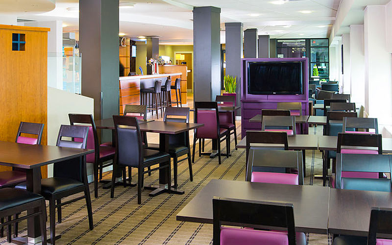 A seating area in the lobby with a purple TV in the middle