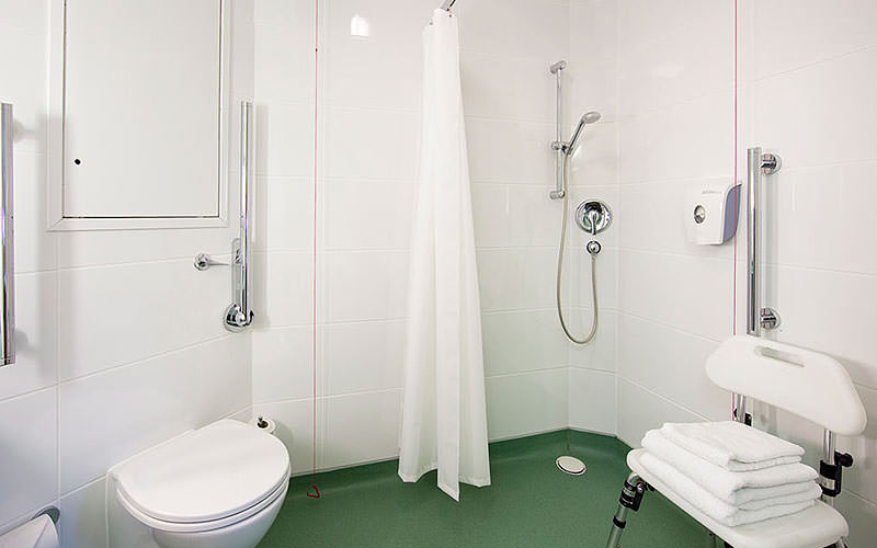 A white wetroom with green floor