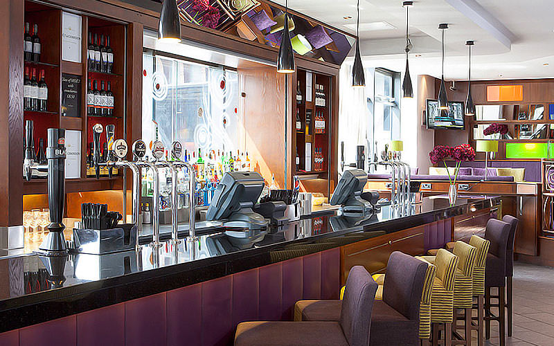 Purple and green bar stools lined up in front of the bar at Jurys Inn Glasgow