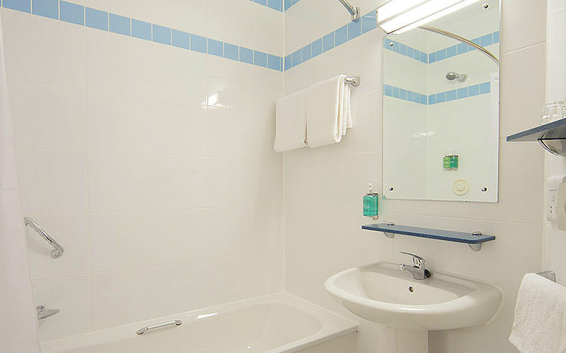A bath, sink and mirror in a white tiled bathroom