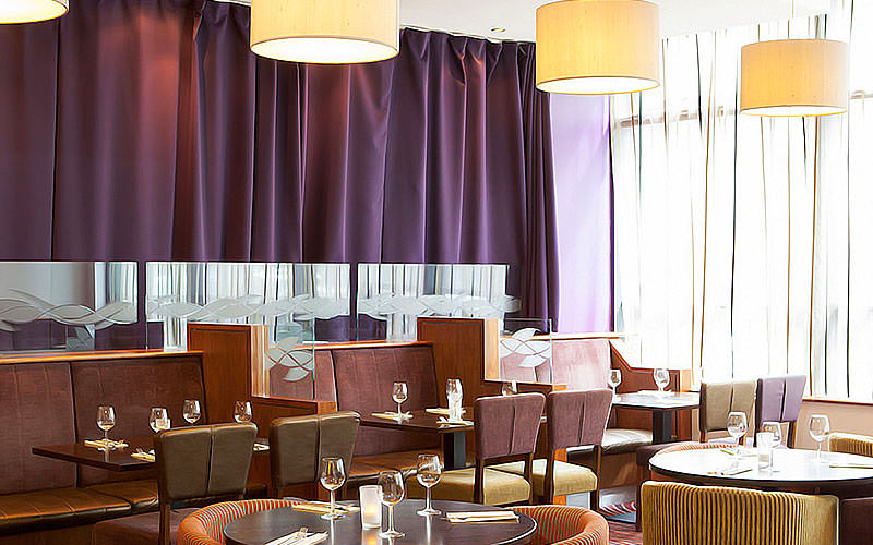 Tables and chairs set up for dinner in the restaurant at Jurys Inn Glasgow, with a large purple curtain in the background