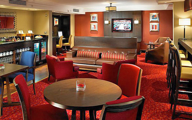 Red and clube chairs, sofas and bar stools around tables in the bar at Marriott Glasgow