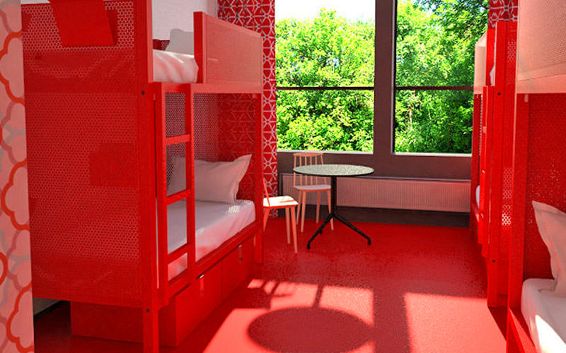 A red room with a large window and two bunk beds against the wall