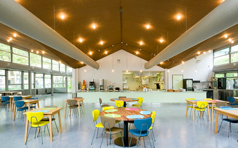 A large dining hall with multicoloured seats and wooden tables