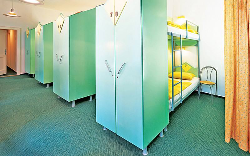 A line of green wardrobes at the foot of bunk beds, in a dorm room