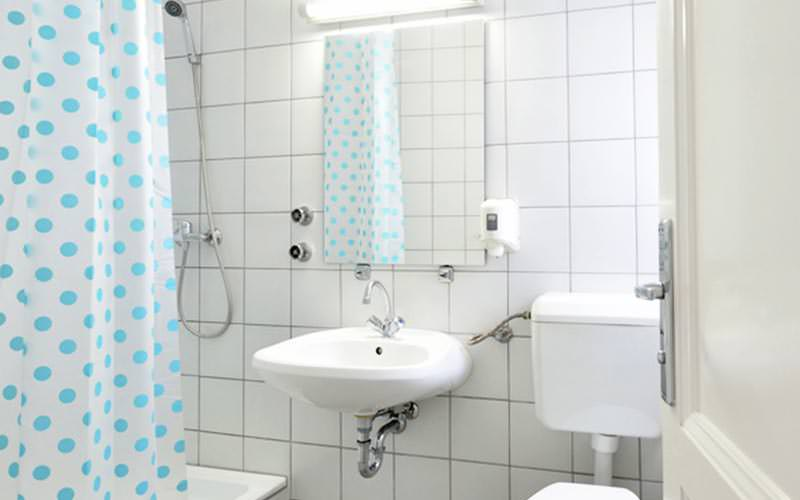 A sink next to a toilet, with a blue and white polka dot shpwer curtain on the other side