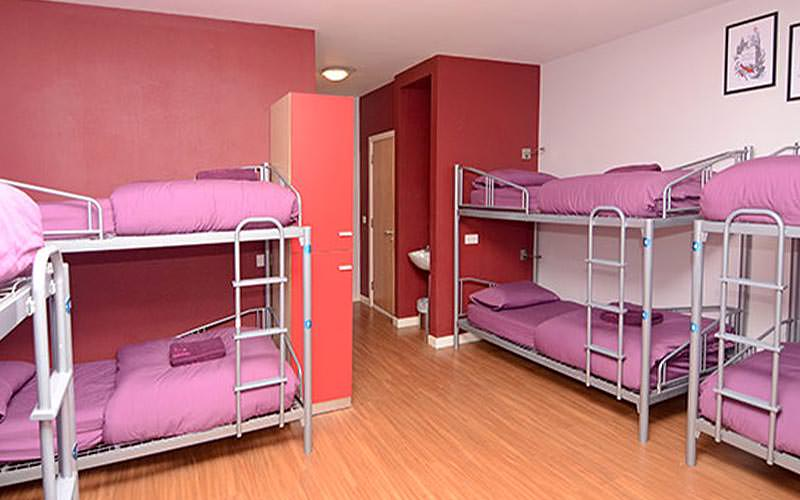 Metal bunkbeds against walls, topped with pink bedding