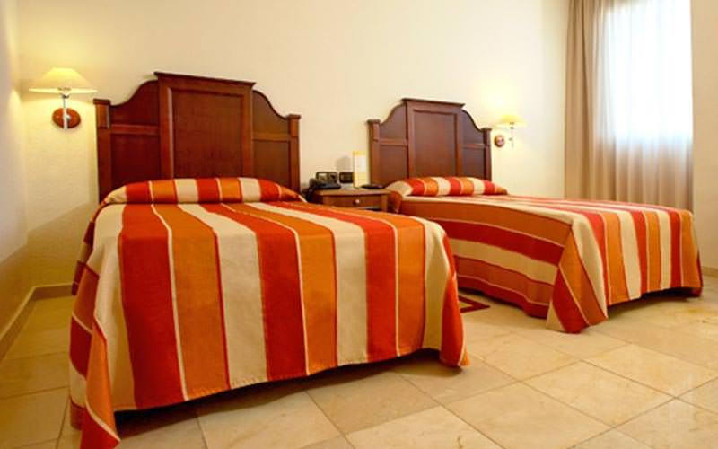 Two single beds with wooden headboards and red striped bedding, in a hotel room