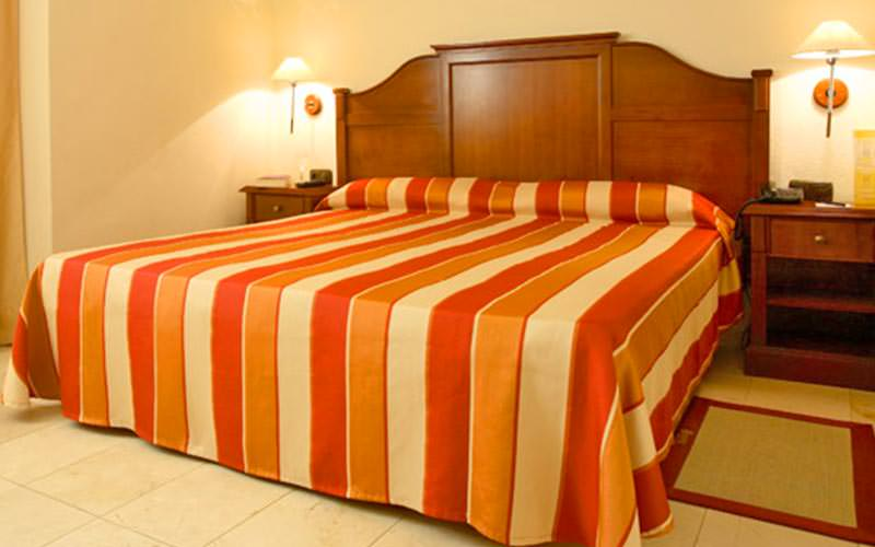 A double bed with striped bedding and two bedside tables at either side