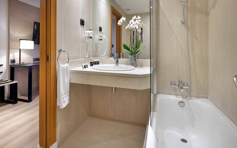 A luxurious bathroom with lilies in a vase on the sink