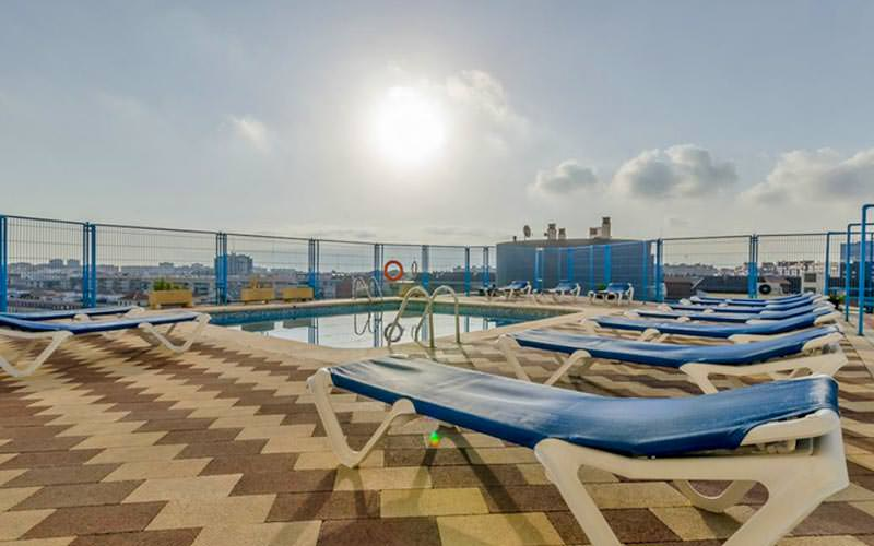 Some sunbeds in a line, with a swimming pool in the middle, under a sunny sky
