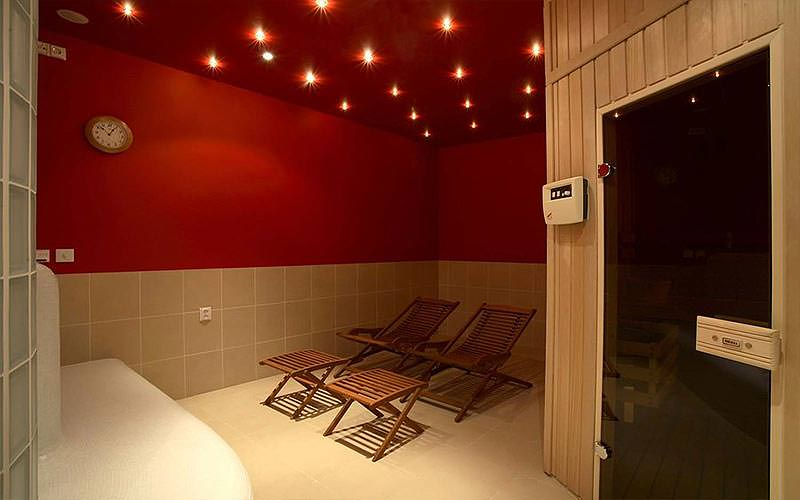 A red sauna with two wooden sun loungers, and a steam room in the corner