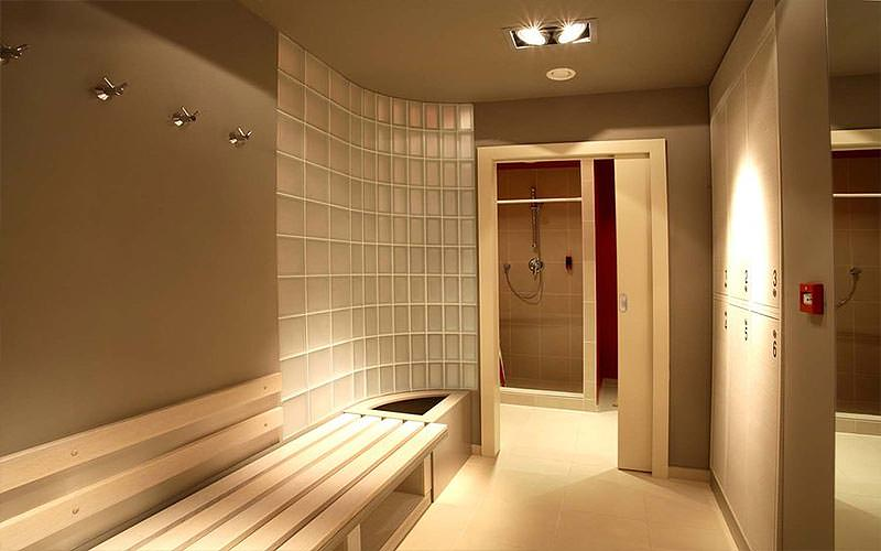 A cream, tiled changing room with bench seating against one wall