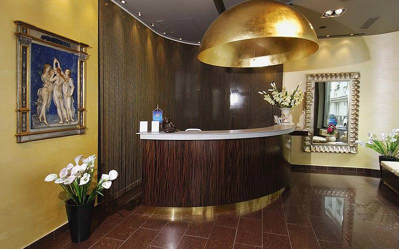 A wooden reception desk, behind a large gold lamp, with pictures on the walls
