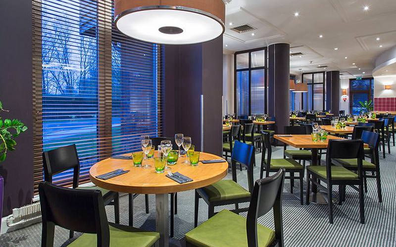 Tables and chairs set up for dinner at the hotel restaurant at Holiday Inn, Cambridge