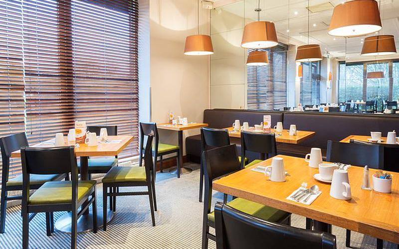 Tables and chairs set up for breakfast at the hotel rstaurant at Holiday Inn, Cambridge