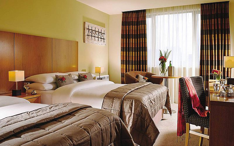 Two double beds in a room with a floor to ceiling window, yellow walls, plush bedding and a desk and chair