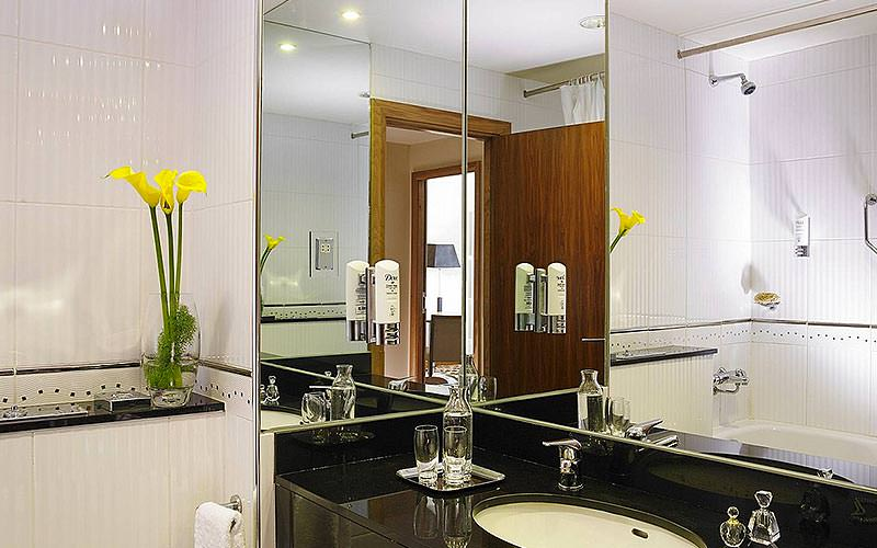 A monochrome bathroom with yellow lilies