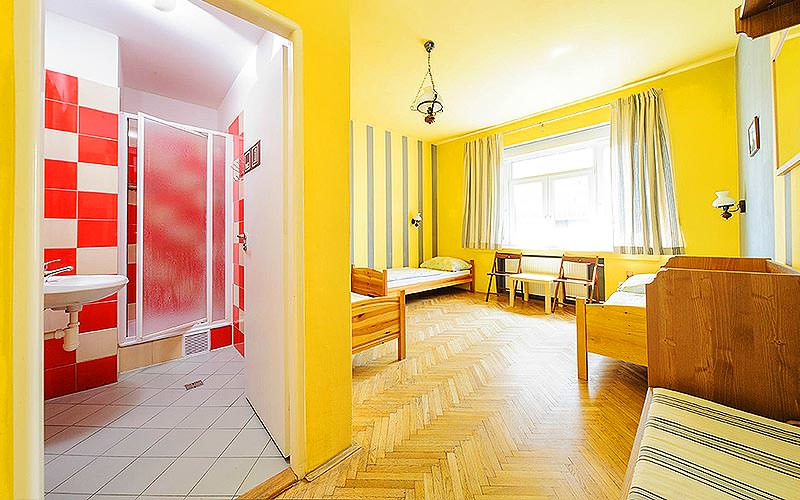 An example guestroom at Hostel Blues with yellow walls and a red bathroom