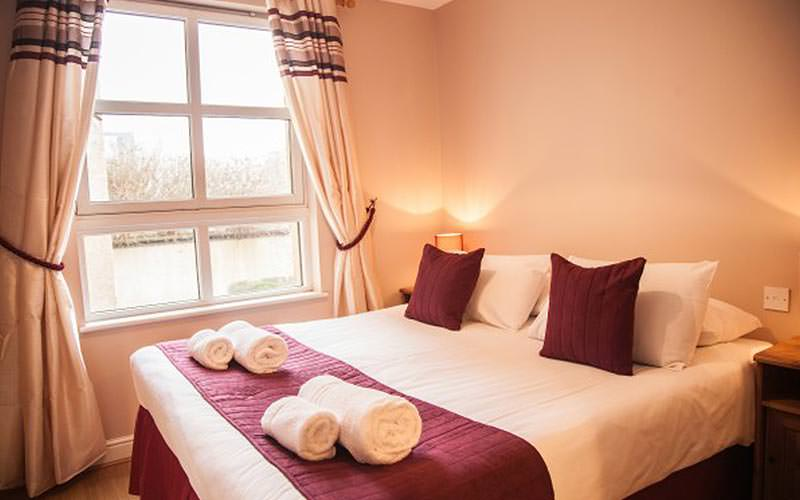 A double bed topped with pink cushions and a throw, as well as white rolled up towels
