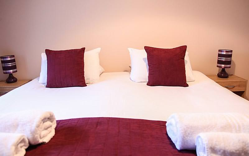 A double bed topped with pink cushions and throws, as well as white rolled up towels