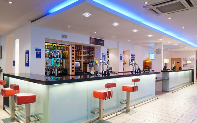 The bar area within the Holiday Inn, with red bar stools and a fully stocked bar
