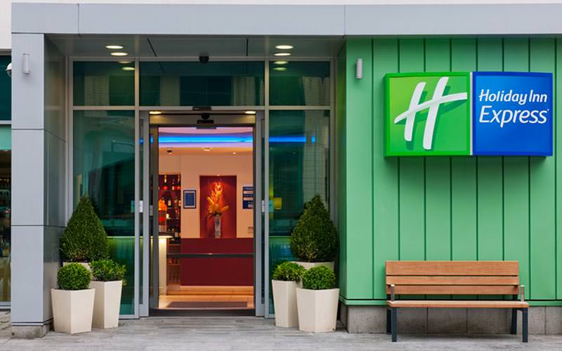 The doorway into the Holiday Inn Express, with a bench outside and some small trees