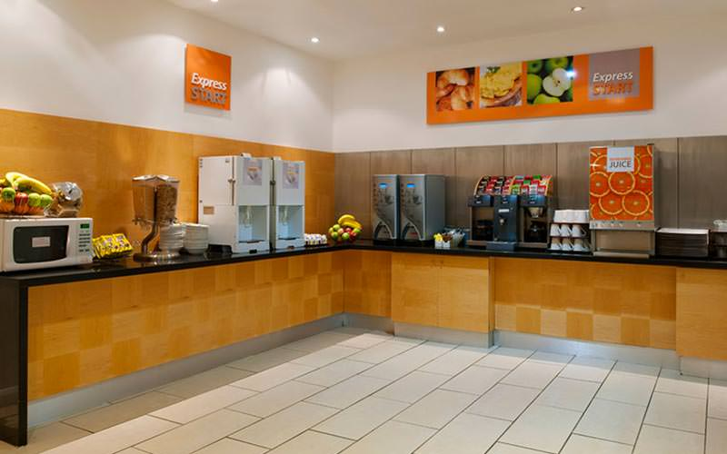 The breakfast buffet area within the Holiday Inn in Newcastle, with cereal, orange juice and a microwave on show