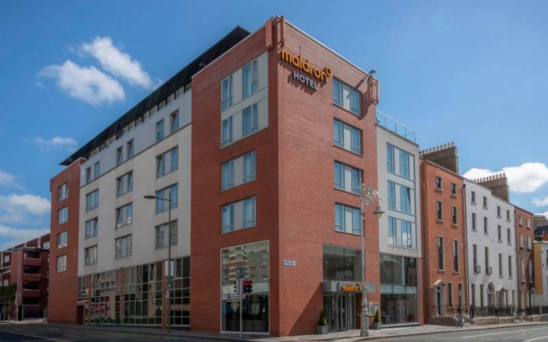 A guest room with two twin beds and a seating area at the Maldron Hotel Parnell Square