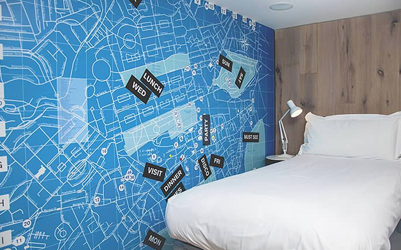 A blue map of Scotland on the wall of a hotel room, with a white single bed in the corner