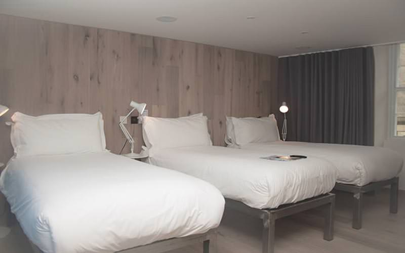 Three single beds in front of a wooden wall in a hotel room