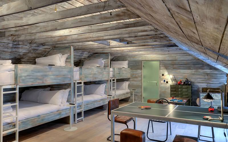 Wooden bunk beds against a wall, opposite storage and a ping pong table