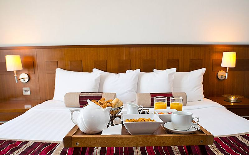 A breakfast tray topped with a teapot, orange juice and food, on a double bed in a hotel room