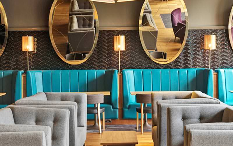 Some teal and grey seating with mirrors above