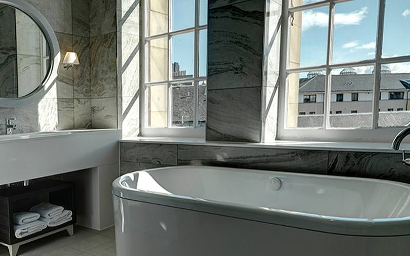 A luxurious bathroom with a nice view out of the window