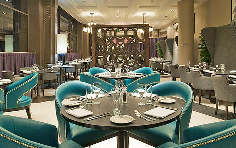 Teal seats in a dining area with tables set for dinner