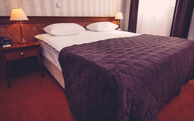A double bed with purple throw and red carpet