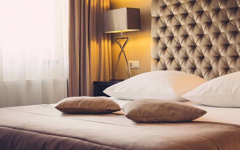 A double bed with a large headboard, with a modern lamp
