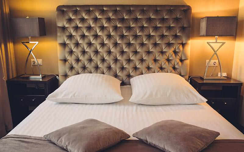 A double bed with large headbaord and modern lamps